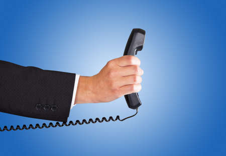 telephone receiver: Closeup of businessmans hand holding telephone receiver against blue background