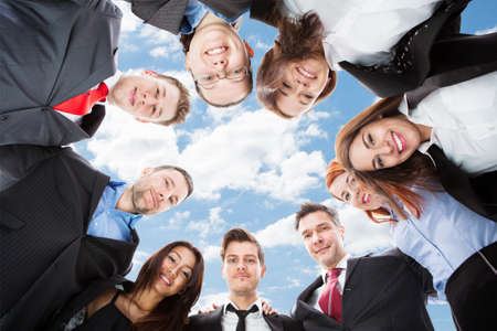 directly below: Directly below portrait of multiethnic businesspeople forming huddle against sky