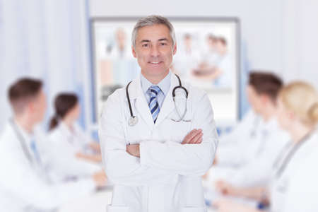 Portrait of senior doctor with arms crossed against team video conferencing in meeting room