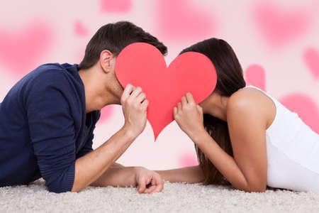novios besandose: Chupito de perfil de la pareja bes�ndose detr�s de coraz�n, mientras que miente en la piel Foto de archivo