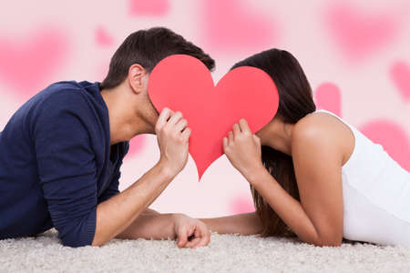 pink hearts: Profile shot of couple kissing behind heart while lying on fur