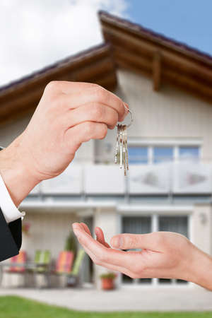 tenant: Cropped image of real estate agent giving keys to owner against new house Stock Photo