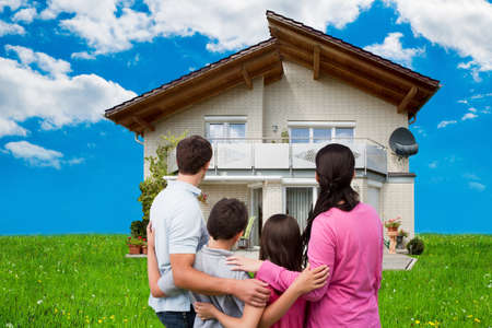 arms around: Rear view of family looking at new house on grassy field against sky Stock Photo