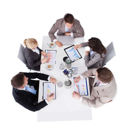 five people: High angle view of business people discussing over financial graphs at conference table against white background Stock Photo