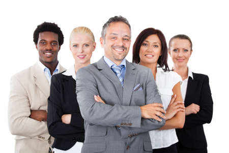 Portrait of confident businessman standing arms crossed with multiethnic team over white background Stock Photo