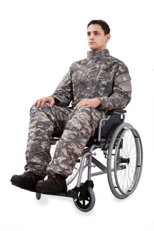 Full length of determined soldier sitting in wheelchair isolated over white background