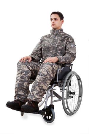 herido: Longitud total de soldado determinado sentado en silla de ruedas aisladas sobre fondo blanco Foto de archivo