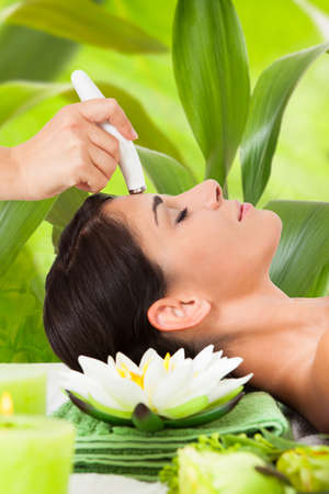 laser focus: Young woman receiving microdermabrasion therapy on forehead against leaves