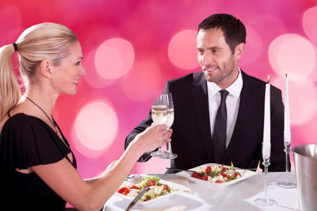 Smiling young couple looking at each other while toasting champagne flutes at restaurant table photo