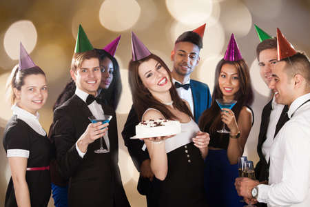 Portrait of happy young woman celebrating birthday with friends at nightclub