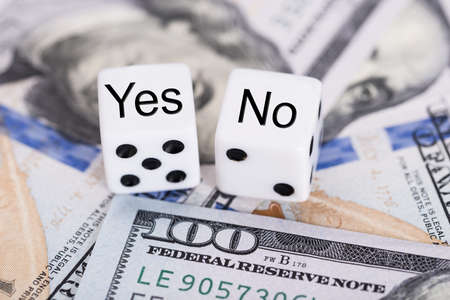 no idea: Closeup of Yes and No dices on dollar bills Stock Photo
