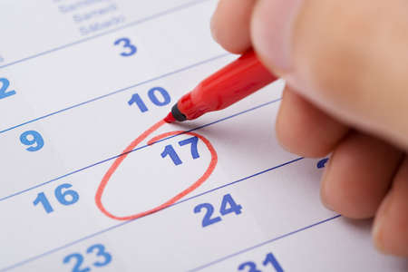 marking: Cropped image of hand marking 17th date on calendar
