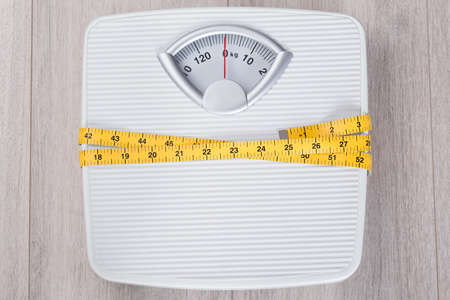 weightloss: Directly above shot of weight scale wrapped in measure tape on floor