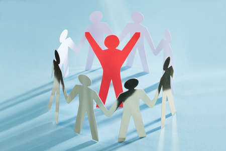 figure out: Successful red paperman surrounded by metal team representing unity isolated over blue background