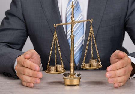 balanza justicia: Secci�n media de hombre de negocios escala de la justicia protegiendo con monedas en la mesa Foto de archivo