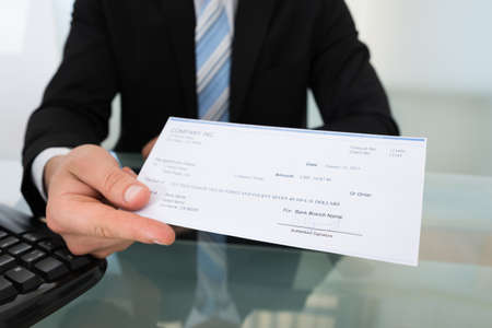 Midsection of businessman giving cheque at desk in office Stockfoto