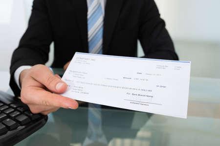 Sección media de hombre de negocios dando cheque en el escritorio en la oficina