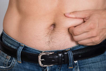 Closeup midsection of man holding fat belly
