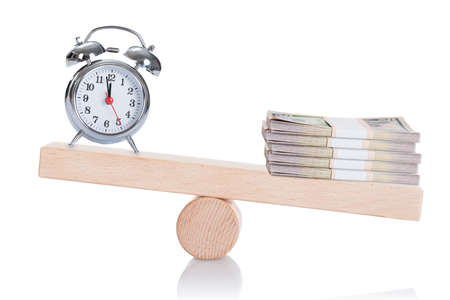 Alarmclock and stacked dollar bundles balancing on seesaw isolated over white background photo