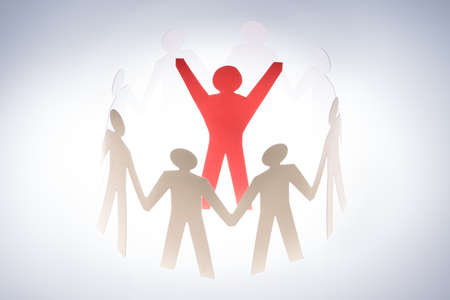 Successful red paperman surrounded by team representing unity isolated over gray background photo