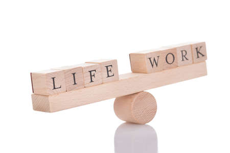 Wooden seesaw representing imbalance between Life and Work isolated over white background Foto de archivo