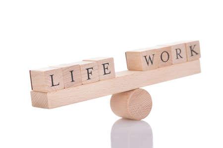 Drewniana huśtawka reprezentujących równowagi między życiem i Pracy izolowanych na białym tle