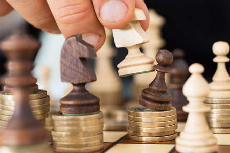 Closeup of hand playing chess stacked on coins photo