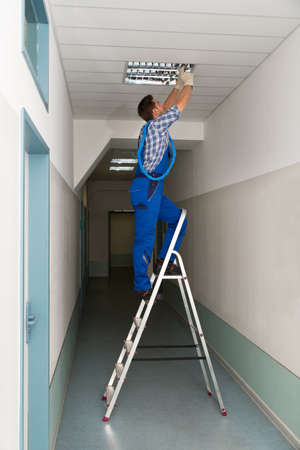 installation: Full length portrait of electrician on stepladder installs lighting to the ceiling in office