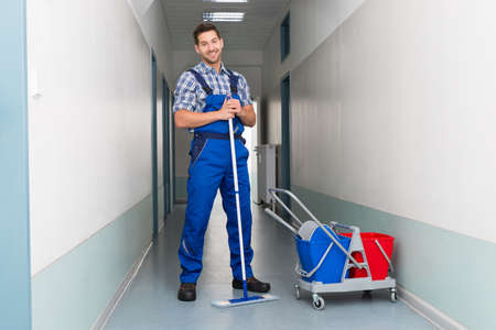 cleaning an office: Full length portrait of happy male worker with broom cleaning office corridor