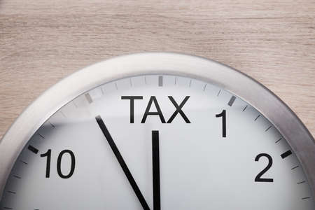 due: Cropped image of clock showing arrival of tax time against wooden wall