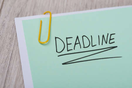 important information: Closeup of Deadline written on green paper note with paperclip