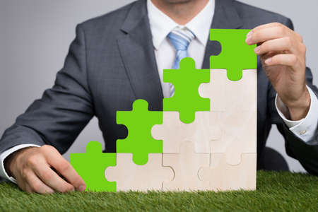 responsibilities: Midsection of businessman holding jigsaw graph on grass representing go green concept
