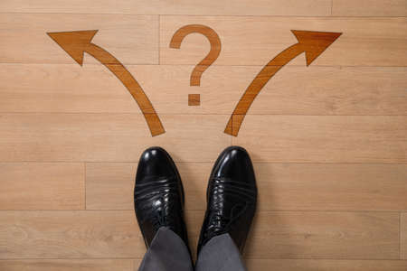 dilemma: Low section of businessman standing in front of left or right arrows and question mark on floor