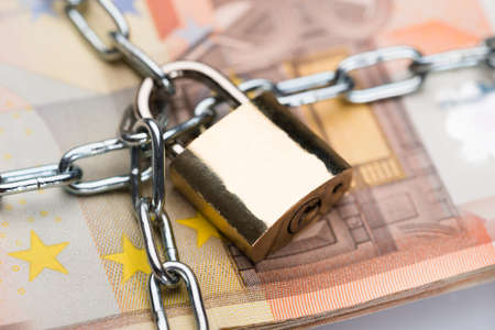 Closeup of metallic chain and padlock around euro banknotes Stock Photo