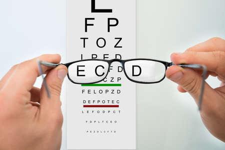 Cropped image of mans hands holding eyeglasses against eyesight test chart photo
