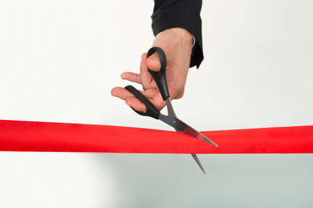 ribbon cutting: Businessmans hand cutting red ribbon with scissors over white background Stock Photo