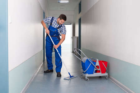 clean floor: Full length of young male worker with broom cleaning office corridor