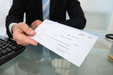 pay desk: Midsection of businessman giving cheque at desk in office Stock Photo
