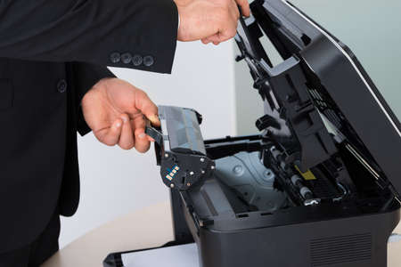 photocopy: Midsection of businessman fixing cartridge in photocopy machine at office