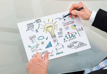 Cropped image of businessman drawing management chart at desk in office