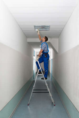 office ceiling: Full length side view of electrician on stepladder installs lighting to the ceiling in office