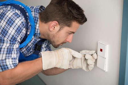 enchufe de luz: Vista lateral del hombre joven reparar interruptor de la luz en el hogar Foto de archivo