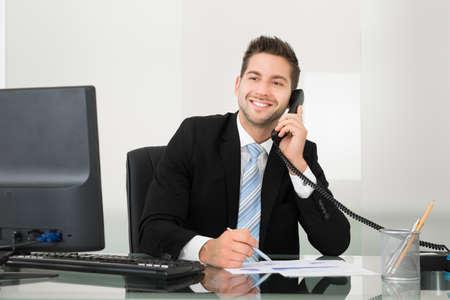 Junger Geschäftsmann, der Diskussion über Dokumente auf Telefon am Schreibtisch im Büro Standard-Bild - 34263883