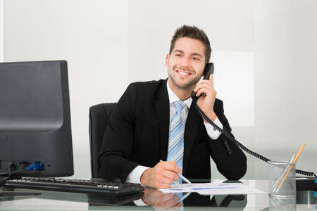 Young businessman discussing over documents on telephone at desk in office