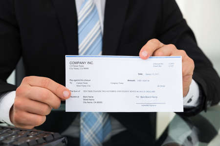 pay check: Midsection of businessman showing cheque at desk in office
