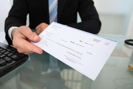 Buik van zakenman geven cheque aan bureau in kantoor Stockfoto