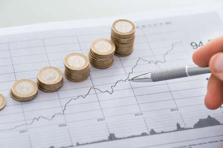 Cropped image of businessman's hand with pen analyzing line and coins graphs on desk