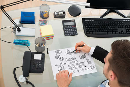 Cropped image of businessman planning strategy on paper at desk in office photo