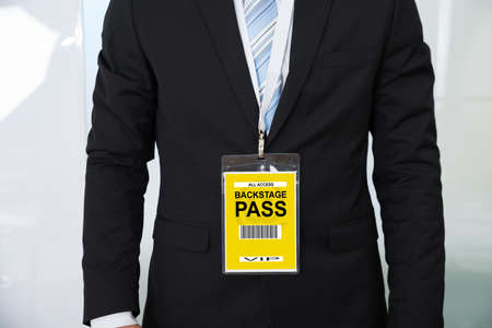 midsection: Midsection of businessman wearing backstage pass in office