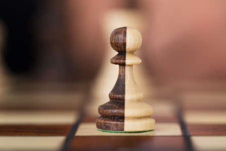 Closeup of merged chess pawns on chessboard Stock Photo